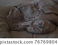 Flattened bed with chocolate-colored cotton linens, closeup view. 76769804