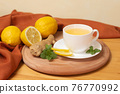 Ginger tea with mint and lemon. Healthy and hot drink. White cup on wooden board on wooden table. Selective focus. 76770992