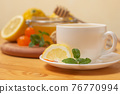 Ginger tea with mint and lemon. Healthy and hot drink. Liquid honey in honey-jar. White cup on wooden background. Selective focus. 76770994