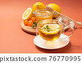 Ginger tea with mint and lemon. Healthy and hot drink. Liquid honey in honey-jar. Crystal cup on bright background. Selective focus. 76770995
