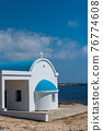Traditional white chapel with a blue roof on the seaside. Agioi Anargyroi, Cyprus 76774608