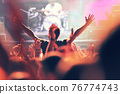 Crowd at a music concert, audience raising hands up 76774743