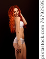 Redhead sexy cabaret dancer in lingerie on a dark background, free space for your text 76792595