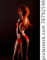 Redhead sexy cabaret dancer in lingerie on a dark background, free space for your text 76792596