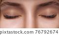 Eyelash Extension Procedure. Woman Eye with Long Eyelashes. Close up, selective focus. 76792674