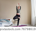 Woman in yoga posture. Online training using 76798619