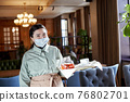 Waitress in mask and with tray standing in cafe 76802701