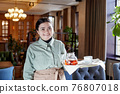 Waitress in apron with tray standing in cafe 76807018