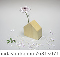 Flower in a wooden model of the house with scattered petals around 76815071