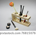 Tulip and brushes for visage stand in a wooden stand on a light background 76815076