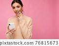 Closeup photo of Attractive cute young brunet woman wearing beige warm sweater standing isolated 76815673