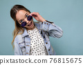 Shot of pretty positive joyful young blonde woman wearing blue jean jacket and stylish sunglasses 76815675