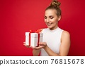 Photo shot of beautiful positive smiling young blonde woman isolated over red background wall 76815678