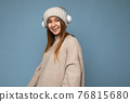 Photo of beautiful happy smiling young blonde woman wearing beige winter sweater and hat isolated 76815680