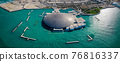 Panoramic aerial view of Louvre museum in Abu Dhabi emirate of the United Arab Emirates at sunrise. View of the building appear to float on the seaside 76816337