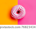 Two sugar glazed donuts on colorful background. 76823434
