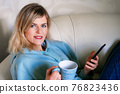 Woman on the couch with coffee mug and cell phone 76823436
