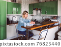business woman looking at mobile phone while at home in the kitchen 76823440