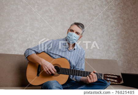 a man in a medical mask plays guitar at home on the couch. Home entertainment in isolation 76825485