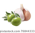 Garlic cloves and green olives isolated on white background 76844333