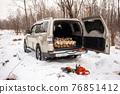 Mitsubishi Pajero/Montero in winter forest with firewood in the trunk 76851412