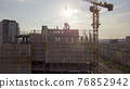 View of the roof of a high-rise building under construction with workers and the background of the city in the setting sun 76852942