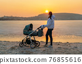 A young mother walks with a stroller for a baby on the shore of a frozen lake, at sunset. 76855616