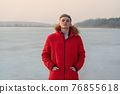 A young guy teenager, in a red jacket, poses and reflects emotionally about life, against the background of a frozen lake. 76855618