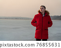 A young guy teenager, in a red jacket, poses and reflects emotionally about life, against the background of a frozen lake. 76855631