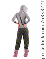 girl in pajamas gray top with a hood, pants with green circles and ugg boots on her legs. white background 76858221