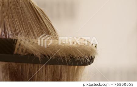 customer's hair strand on a black hairdresser comb 76860658