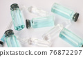 Vial vaccine, top view of glass ampoules with transparent and blue liquid lying on white background, global vaccination concept 76872297
