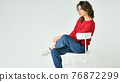 Studio portrait of young woman in red knitted sweater and earring sitting on a chair on white background 76872299