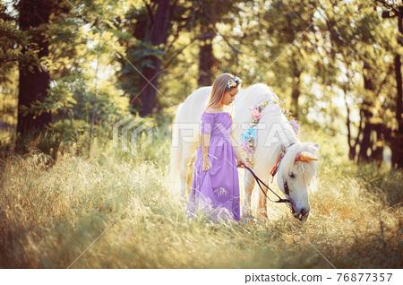 Girl in purple dress hugging white unicorn horse. Dreams come tr 76877357