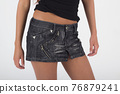 girl in a short denim gray skirt close-up on a white background 76879241