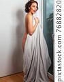 Joyful naked woman at the balcony door 76882820