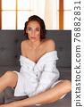 Adult woman sitting in bathrobe 76882831