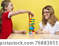 A happy family playing a round of game removing wooden blocks from tower with their lovely daughters. Mother and daughters have fun playing the tower game. 76883655