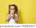 Little girl drinks yogurt from a glass isolated on yellow background. Healthy eating concept. Banner with copy space. 76883657