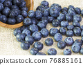 Blueberries in a wooden bowl scattered on a rustic table 76885161