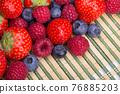 Strawberries, blueberries, raspberries scattered top view 76885203