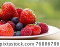 Pile od strawberries, blueberries, raspberries on green background 76886786