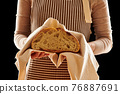 Baker holding loaf of homemade bread 76887691