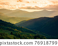 rural landscape in mountains at sunset. dramatic weather above the distant valley in springtime. green fields and trees on the hill. beautiful nature scenery with clouds on the sky 76918799