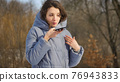 Lady in blue coat is sending audio voice message explaining something on smart phone at outdoor talking to mobile assistant. Girl using smartphone voice recognition and dictation 76943833