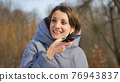 Lady in blue coat is sending audio voice message explaining something on smart phone at outdoor talking to mobile assistant. Girl using smartphone voice recognition and dictation 76943837