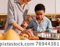 Woman and her multiracial son chopping vegetables on wooden board 76944361