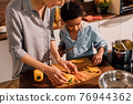 Boy holding knife and cutting fresh vegetables in kitchen interior 76944362