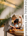 Woman teaching boy cooking, while helping chopping vegetables for dinner 76944365