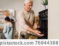 Man opening the oven while preparing to the baking dish for the dinner 76944368